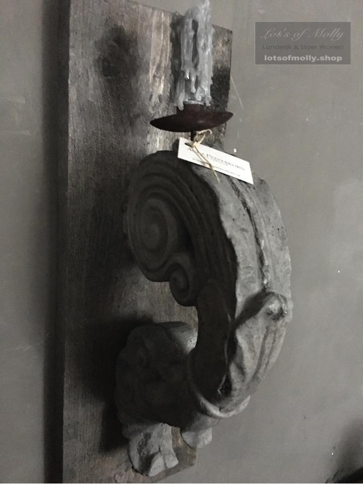 Betonnen ornament kandelaar op houten plank